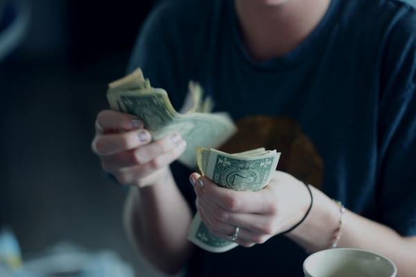 Woman counting US dollar bills.